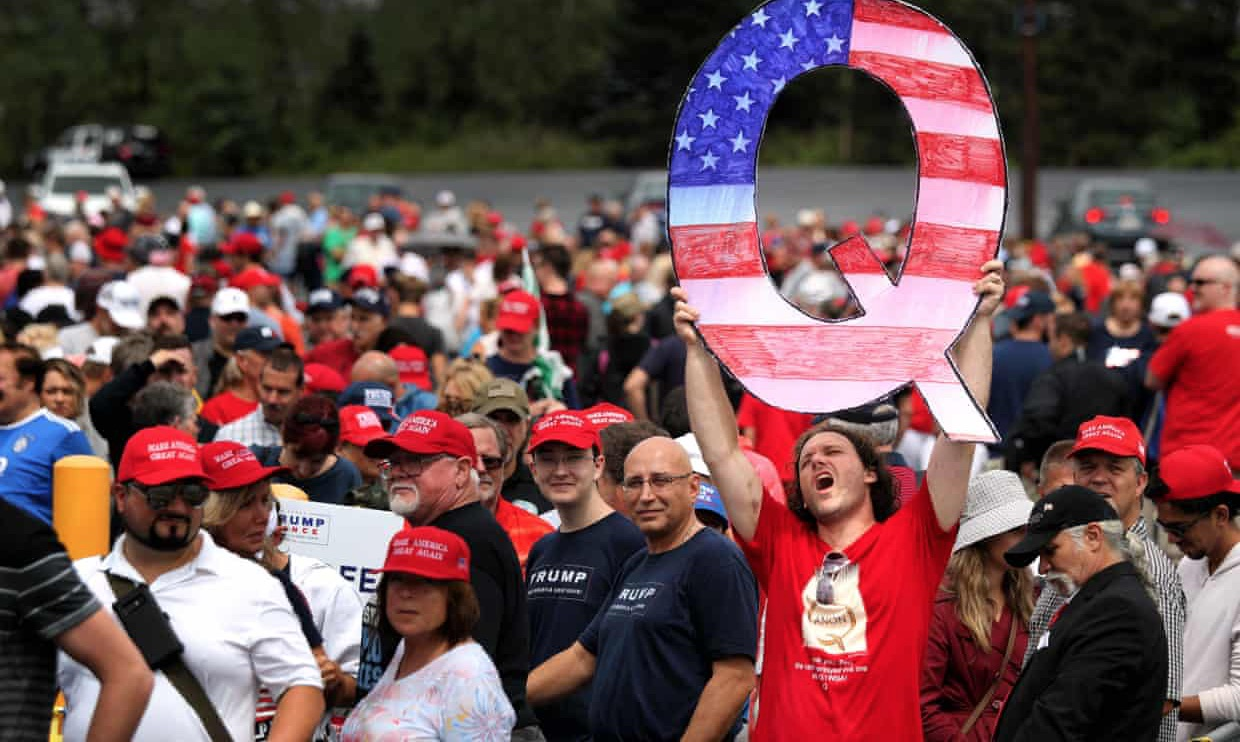 "a photo of a man at a political rally holding a large cardboard cutout of a ""Q,"" representing his support for the qanon conspiracy"